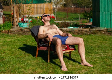 A man in swimming trunks sunbathes on a ancient armchair in the yard of a country house