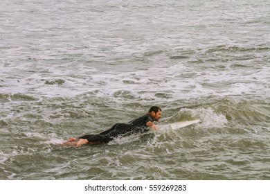 Man swims with a board on the shores of Mar del Plata, Argentina. January 14, 2017
