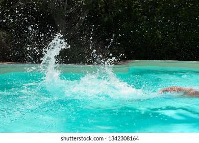 Man swims in a pool splashing the water.