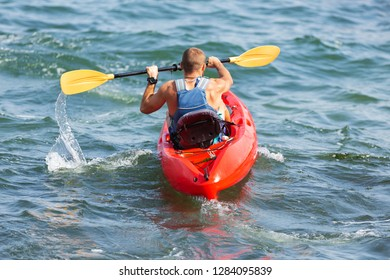 man swims in a red kayak, paddles, splash of water, lifestyle, concept