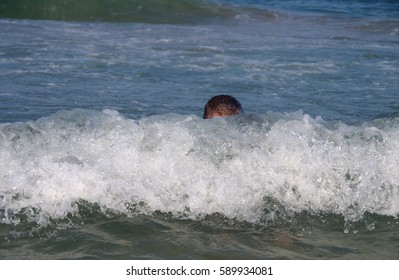 A man swims in the sea in big waves