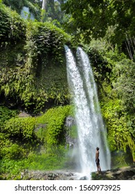 A man in swimsuit standing under two levelled waterfall in Lombok, Indonesia. Tiu Kelep Waterfall is surrounded by lush green plants from each side. Long and powerful waterfall. Beauty of the nature.
