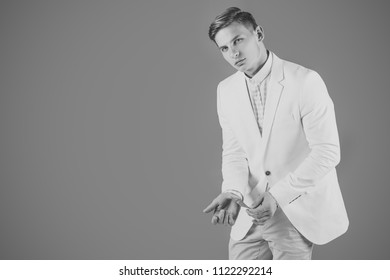 man swindles. Man hiding business or bank card in sleeve. Businessman posing in white jacket. Manager wearing casual suit on grey background. Fashion and information concept. Banking and saving, copy