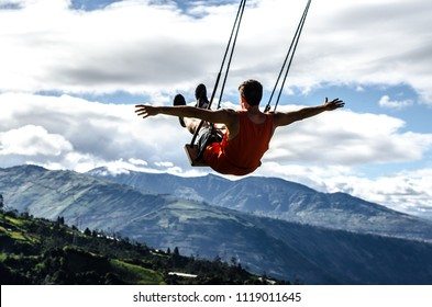 Man swinging on swing at the end of the world, baños de agua santa ecuador (A person swing over the jungle in Ecuador.)