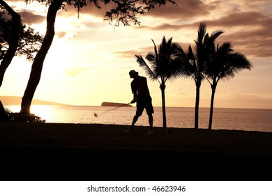 A man swings his golf club amidst a tropical setting. Palm trees and the ocean are in the background. Horizontal shot.