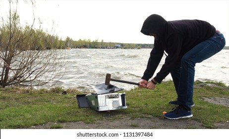 Man swings sledge hammer into printer, compuer and monitor on nature background with grasss, river, waves and sky. Concept of nature victory over technology