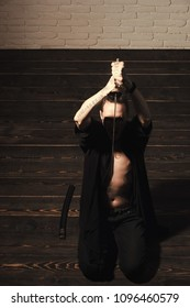 Man with sword and open belly preparing for harakiri. Samurai warrior with katana sitting on wooden floor. Suicide ritual concept. Honor and dignity. Reincarnation and rebirth.
