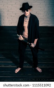 Man with sword standing on wooden floor barefoot, top view. Warrior in black hat and open clothes showing tattooed torso. Honor and dignity. Samurai, buddhist concept. Harakiri, suicide ritual.