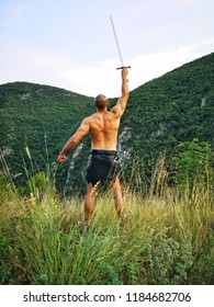 Man With Sword / Strong Natural Musculus Warrior Rising His Hand with a Sword, Shouting Charge! / Ancient Knight / Rocky and Green Mountains as Background