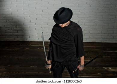 Man with swords standing on wooden floor. Warrior in black hat and clothes, top view. Honor and dignity. Samurai, buddhist concept. Harakiri, suicide ritual.