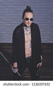 Man with swords standing on wooden floor, top view. Harakiri, suicide ritual. Samurai, buddhist concept. Warrior in black sunglasses and open clothes showing tattooed torso. Honor and dignity.