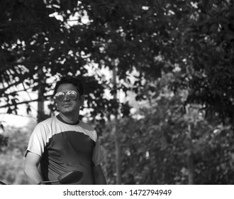 Man in a t shirt and sunglass standing in a place unique photo
