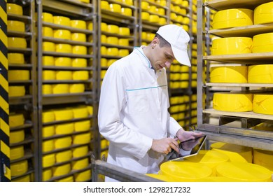man with a tablet in his hands is in a warehouse of cheeses