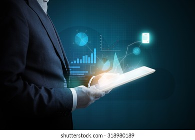 man with tablet pc analyzing virtual diagrams of financial activity over dark background