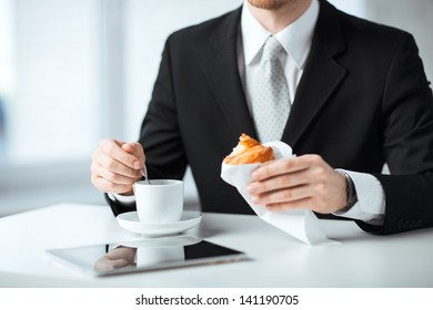 man with tablet pc, cup of coffee and croissant