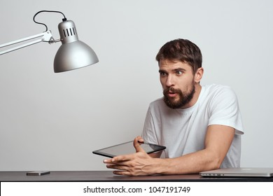 a man with a tablet sits at a table