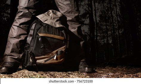 Man in tactical outfit standing over a backpack with camping and tactical gear on night forest background.