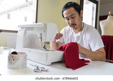 man tailor sitting on sewing machine and use needle with white thread knit on red cloth. portrait of male designer in workshop