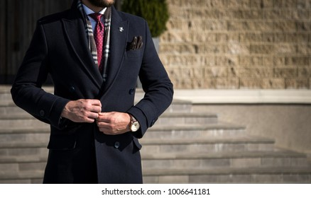 Man in tailored trench coat with leather gloves in his pocket and suit posing outdoors while buttoning his coat