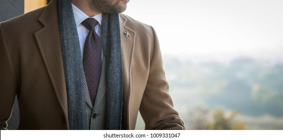 Man in tailored trench coat and suit posing outdoors