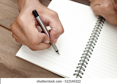 The man take a him hands writing  the blank book on wood table.
