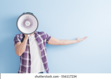 man take microphone and show something to you isolated on blue background