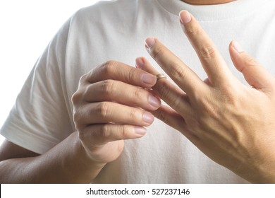 Man take off his wedding ring on white background