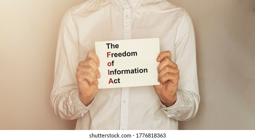 man take a paper with text The Freedom of Information Act FOIA on the shirt with office background