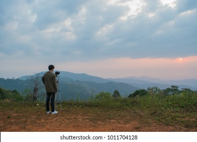 the man take a photo of sunrise on the mountain
