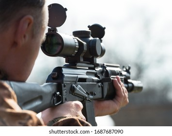 A man takes aim and shoots from Kalashnikov. Over the sholder.