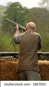 Man takes aims and fires at the clay pigeon
