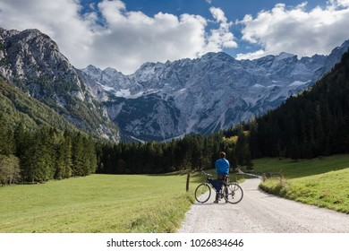 A man takes a break from cycling to enjoy the view on this gravel road and open green fields. There is a vast mountain range, with a shadow cast over the forest on the right side.