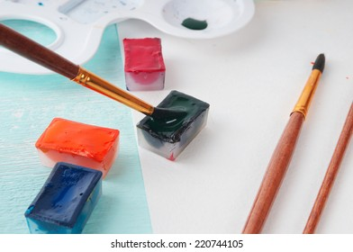 A man takes a brush watercolor paint before painting
