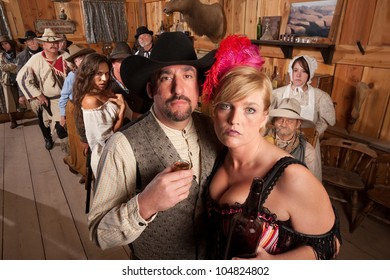 Man takes a drink with bar maid in old west tavern