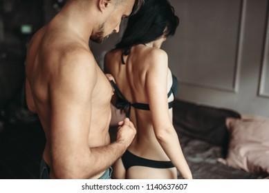 Man takes off bra from his woman, seductive scene