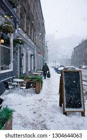 A man takes out the trash while a snowstorm covers the streets with white snow and obscures the view of Edinburgh castle.