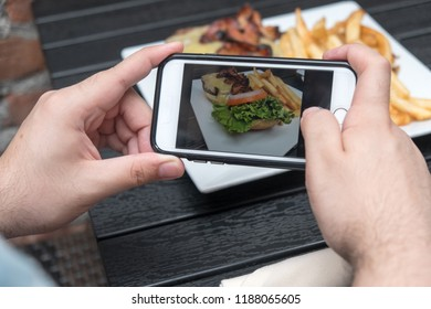 Man takes a photo of his lunch with his smartphone. Mobile phone photography. Taking a photo with phone of hamburger, french french fries on white plate on black table outside.