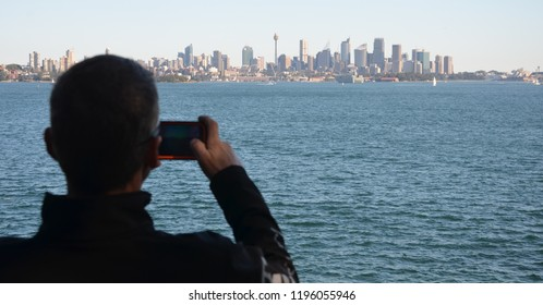 Man takes photos of Sydney panorama with his mobilephone. View of Sydney skyline and Sydney Harbour from Nielsen Park.