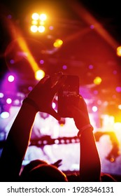 Man takes a picture of the show at the concert hall using a smartphone