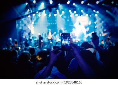Man takes a picture of the show at the concert hall using a smartphone - Shutterstock ID 1928348165