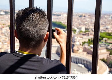 man takes a picture of St. Peter's Square in the Vatican on his smartphone through a lattice on the dome of St. Peter's Cathedral