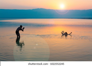 A man takes pictures of a girl who is bathing in a dead sea in Israel. Photo for social networks. Sunset on the beach. Sunrise. Gold sand. Winter. January.