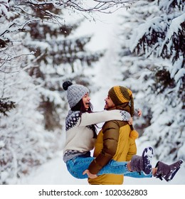 Man takes woman on his arms whirling in a winter forest covered with snow
