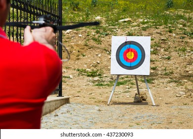 Man taking aim with a crossbow at an outdoor target on a shooting range, over the shoulder view with focus to the target