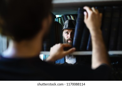 Man taking book from library bookshelf and sees bearded man. Peeping man in black hat among bookshelves