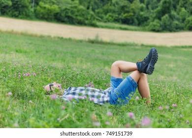 Man taking a break in nature / green field.