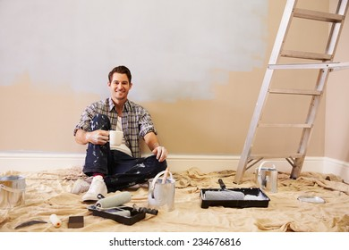 Man Taking A Break Whilst Decorating Room