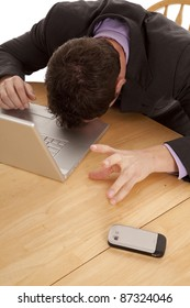A man taking a break from the work and stress by laying his head on the laptop.