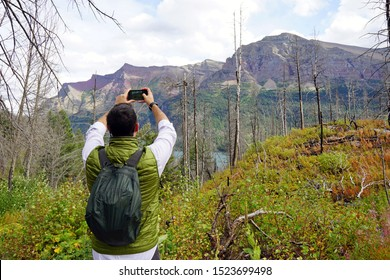 Man taking a cell phone photo of a scenic hike in Glacier National Park