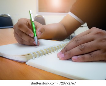 Man taking exam writing answer in classroom for education and literacy concept